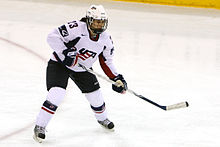 "A female ice hockey player, wearing a white jersey with a stylized ""USA"" on the chest, is on the ice with her stick slightly raised off the surface, looking forward."
