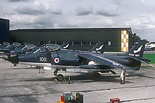 Line-up of jet aircraft, all painted in metallic blue, facing left of photograph. In the distance is a tall, dull-coloured warehouse.