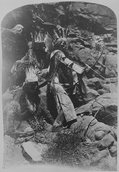 File:A Paiute drawing his bow and arrow, two others in festive costume, 10-1872 - NARA - 517727.jpg