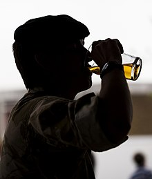 Silhouetted man drinking a glass of beer
