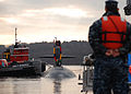A U.S. Sailor stands by to assist fast-attack submarine USS Dallas (SSN 700) in mooring to the pier at Naval Submarine Base New London in Groton, Conn., Dec 111214-N-AW342-026.jpg
