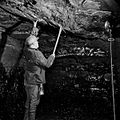 A miner tests the stability of the tunnel roof.jpg