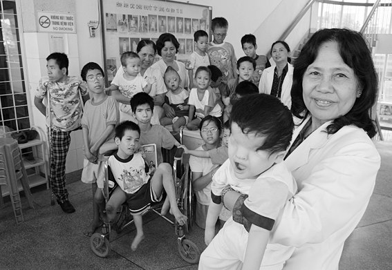 A vietnamese Professor is pictured with a group of handicapped children