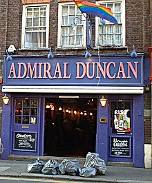 "A blue/purple public house with large prominent signage as ""The Admiral Duncan"". A rainbow flag is above it, and a number of garbage bags are on the pavement in the foreground."