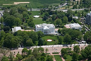 White House - Aerial view of the White House complex, viewed from north. In the foreground is Pennsylvania Avenue, closed to traffic. Center: Executive Residence (1792-1800) with North Portico (1829); left: East Wing (1942);  right: West Wing (1901), with the Oval Office (1909) at the south-east corner