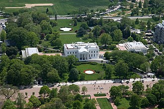 White House - Aerial view of the White House complex, from north. In the foreground is Pennsylvania Avenue, closed to traffic. Center: Executive Residence (1792–1800) with North Portico (1829) facing; left: East Wing (1942);  right: West Wing (1901), with the Oval Office (1909) at its southeast corner