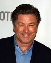 Alec Baldwin, a caucasian male in his early-50s with dark uncombed hair, wears a black suit with a blue shirt with the collar open. He smiles and stands in front of a white background with grey font.