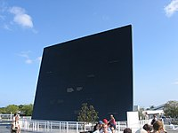 Large square black wall with people standing in front