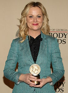 Amy Poehler faces forward wearing a light blue blazer. She holds a small circular award by its base.