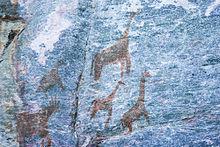 stenmålning som visar långhalsade fyrfötter, i brunt på en blå bakgrund