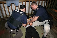 Two police officers seen from above and behind, on their knees putting handcuffs on a prone man between them.