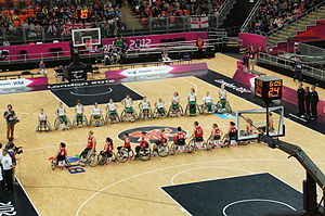 Parallel lines of two teams of players in wheelchairs, one in red, the other in green and white. They are on a basketball court, surrounded by media, official in black, and spectators.
