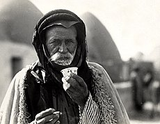 "Photo post-card by V. Derounian, 1930, of an elderly inhabitant of a Beehive village in Aleppo's district in northern Syria, sipping the traditional bitter murra Arabic coffee and smoking a cigarette. His over-coat is lined with wool, and serves as a mattress and a blanket (sleeping bag) when traveling, and known locally as furwa, and hence the western word of ""fur"". The black Kaffiya on his head conserves the heat from the sun in the cold climate of the north."