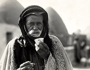History of coffee - Syrian Bedouin from a beehive village in Aleppo, Syria, sipping the traditional murra (bitter) coffee, 1930