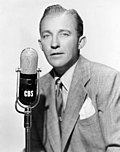 Black and white publicity photo of Bing Crosby--a white man with light eyes wearing a gray suit and tie in front of a microphone - 1951 .