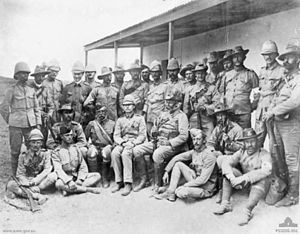 Group of soldiers gathered in a semicircle for an informal portrait. They are wearing a variety of different headgear including pith helmets, garrison caps and slouch hats. An unsmiling Chauvel wears a bandolier and slouch hat, and holds a rifle.