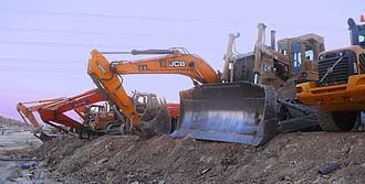 Heavy equipment - Bulldozer, excavators and other heavy equipment vehicles parked near a quarry