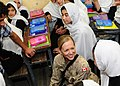 Canadian Lt. Jenna Martin, center, speaks with Afghan students after Afghan National Civil Order Police and Coalition advisors handed out donated school supplies. (4678254750).jpg