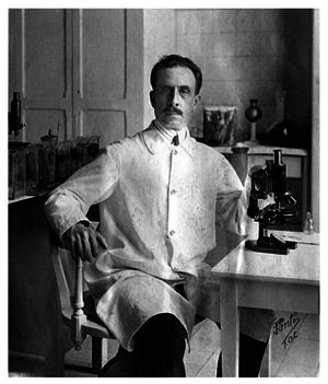 Black and white photo of Charlos Chagas, in his lab coat, sitting next to his microscope and surrounded by flasks and jars