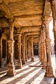 Carved stone pillars forming the corridor at kutub minar complex.jpg