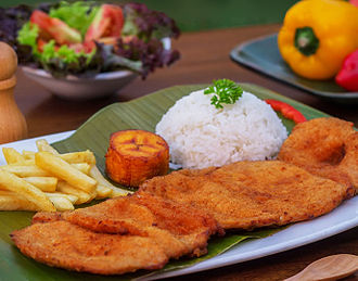 "Colombian cuisine - Cutlet ""Valluna"", a typical dish of the Valle del Cauca region of Colombia and the Afro-Colombian culture of the area near the Pacific Ocean. It includes a milanesa, usually prepared with a lean pork loin. Beef or chicken can also be used. Traditional accompaniments include rice, sliced tomatoes, onions, chopped fried plantains or fries and a drink called ""Lulada"" made with lulo fruit, water and sugar"