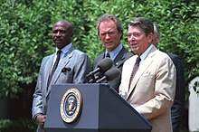 Photographie de Louis Gossett, Clint Eastwood et Ronald Reagan en plein discours, devant un pupitre qui porte un micro