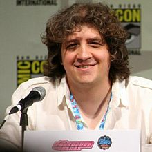 A Caucasian male wearing a white shirt sits in front of a microphone, smiling. He has large, curly brown hair which almost covers his eyes.