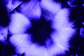 Gemology - The curvature observed in this synthetic color-change sapphire is due to a process known as the Verneuil Process or, flame fusion. During this process, a fine crushed material is heated at extremely high temperatures. The crushed material is then melted which drips through a furnace onto a boule. This boule where the corundum cools down and crystallizes, spins and thus causes the curved striations. Natural corundum does not form this way and lacks the curved striations.