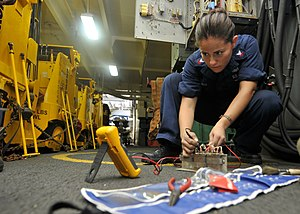 Defense.gov News Photo 110723-N-EE987-125 - Petty Officer 2nd Class Maria Arreedondo uses a flow divider while fixing a forklift battery charging station in the hangar bay of the aircraft.jpg