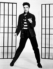 A young man dancing, swiveling his hips. He has dark hair, short and slicked up a bit. He wears an unbuttoned band-collared jacket over a shirt with bold black-and-white horizontal stripes. Behind him, on either side, are a pair of barred frames, like prison doors.