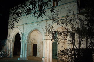 San Clemente Abbey - Night view of the abbey church's façade.