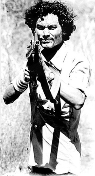 "Farabundo Martí National Liberation Front - A Farabundo Martí National Liberation Front (FMLN) soldier takes aim during a wartime ""road advisory"" near Suchitoto, El Salvador (1984)."