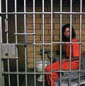 Female prisoner shackled in her small cell.jpg