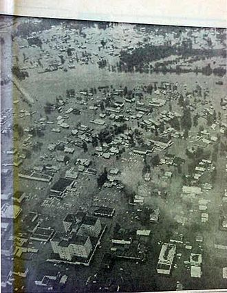 History of Fairbanks, Alaska - Aerial photo, looking roughly eastward, as downtown Fairbanks is inundated by floodwaters, 1967.  The Northward Building is at lower left.  The Wendell Street Bridge is at upper left.  The (by now submerged) Chena River runs across the top half of the photo, with Graehl and Bentley Island (Island Homes) to the north and east (or in the photo, above) the river.