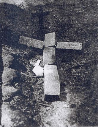 Wola massacre - Ashes of 4,000 Wola massacre victims murdered at the Franaszek factory buried in a hole in the ground and commemorated by provisional cross