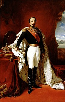 Portrait of Napoleon III. He is dressed in black and white in front of a red wall.