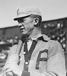Photograph of Phillies pitcher Grover Cleveland Alexander, resting a bat on his right shoulder, taken from his left side