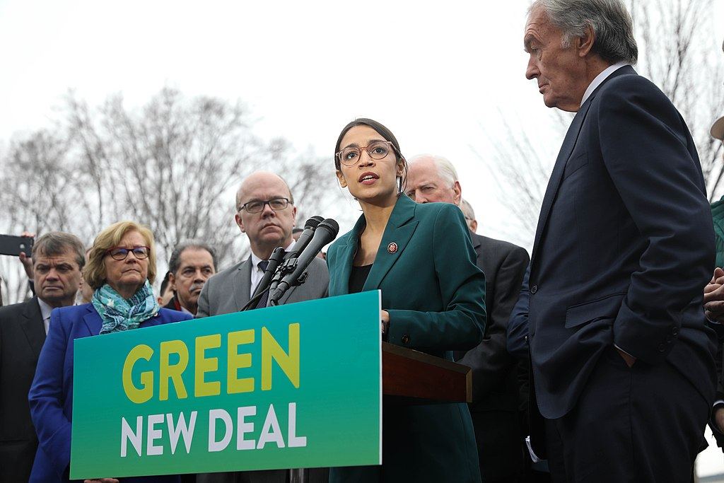 photo people at a podium, speaking, sign reading Green New Deal