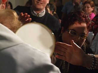 Catholic Charismatic Renewal - The Eucharist being elevated during a Catholic Charismatic Renewal healing service, in which the faithful not only pray for spiritual and physical healings, but also for miracles.