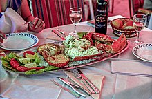 Photo of restaurant table holding a platter featuring unshelled lobster legs and claws