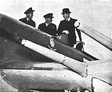 Three men stand next to a fighter aircraft and look at it.