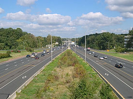 Both sides of a highway with a grass plot in the middle of the roads. Street lamps surround the middle and several cars are on the roads. The roads have an HOV diamond on them.