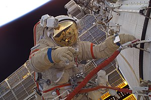 Orlan space suit - Attired in a Russian Orlan-M spacesuit, astronaut John Phillips participates in an extra-vehicular activity. Cosmonaut Sergei Krikalev is seen in Phillips' helmet visor.