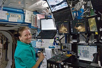 Expedition 24 - Shannon Walker is pictured near the robotic workstation in the Destiny laboratory during the EVA 2 on 7 August 2010.