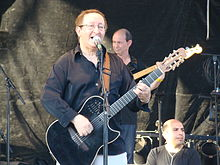 Photo en couleurs d'un guitariste chantant avec un micro sur pied.
