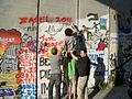 "International Volunteers Writing ""Zajel"" at the apartheid wall.jpg"