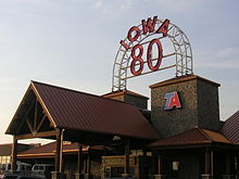 "A large building with a high-peaked roofline. A large neon sign reads ""Iowa 80""."