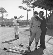 Two white men in baseball uniform with back to camera watch a black baseball player take batting practice