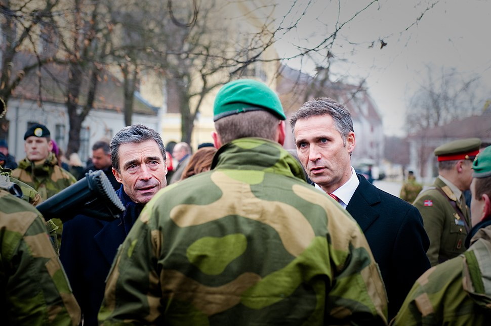 Two gray haired older men talk with a soldier wearing camouflage and a green beret who is facing away.