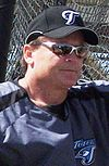 Man in sunglasses and baseball uniform leaning against a fence